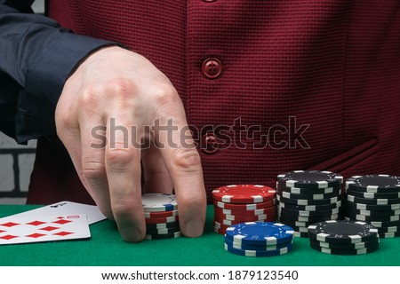croupier's hands are taking chips from the poker table, close-up