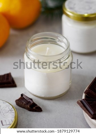 Aroma candle in a glass jar with the aroma of chocolate. The aroma of chocolate. winter atmosphere. winter scents. The aroma of citrus and chocolate. #1879129774