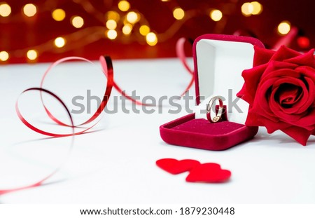 Banner. Gold ring, wedding ring in red box and , red rose on white-red background with beautiful bokeh. The moment of a wedding, anniversary, engagement, or Valentine's Day. Happy day. Royalty-Free Stock Photo #1879230448