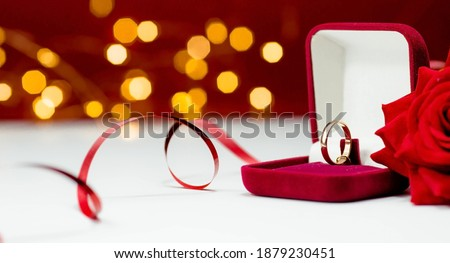Banner. Gold ring, wedding ring in red box and , red rose on white-red background with beautiful bokeh. The moment of a wedding, anniversary, engagement, or Valentine's Day. Happy day. Royalty-Free Stock Photo #1879230451