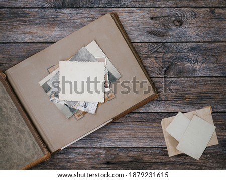 Clear blank photo frames to placed your pictures or text on old family album on wooden board background in retro style. Family traditions, memories and nostalgia concept. Antique album with old photos Royalty-Free Stock Photo #1879231615