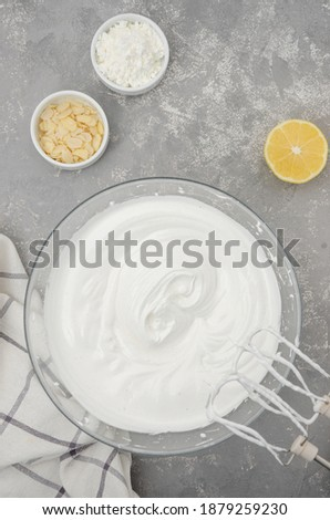 Cooking meringue Pavlova roll cake. Whipped egg whites with sugar in a bowl on a gray concrete background. Recipe step by step. Vertical, Top view
