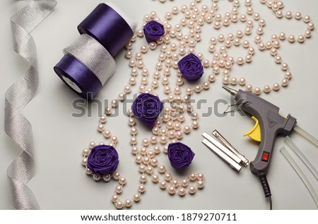 With your own hands.Tapes,cloth, glue gun.Hat hair clip.Crafts.DIY. Shiny ribbon,cones,handcraft tool, ribbon beads on a gray background.Winter crafts. Handmade.Holiday crafts,blue.Blue fabric roses Royalty-Free Stock Photo #1879270711