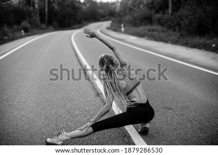A young woman warms up before jogging on the road. Black and white photo.