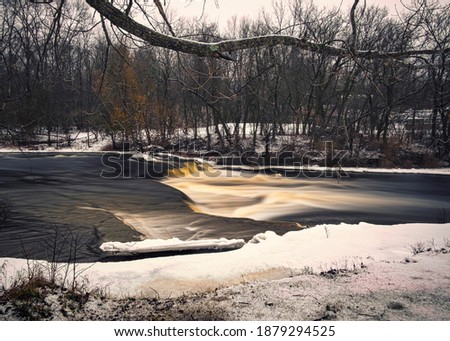 A winter cascade in rural Ontario Canada with the Napanee river exposing flat limestone rock through a winter landscape setting.
