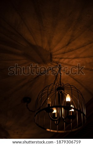 dark interior vertical picture with lights and shadows from chandelier object warm atmospheric background indoor view