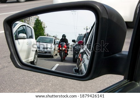 A red, sporty, motorcycle moves between the lane, dangerously close to cars. Royalty-Free Stock Photo #1879426141