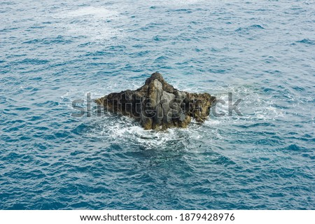 Single rock in the middle of the ocean. Rocky ocean shore. Sea wave background. Rocky cliff Madeira island landscape. Turbulent ocean hitting the shore. Madeira rocky shore. Lava pools landscape. Royalty-Free Stock Photo #1879428976