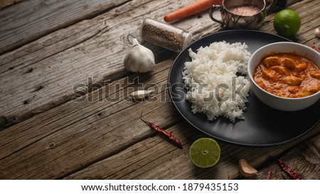 Close-up side view of plate with delicious chicken tikka masala curry and rice on rustic wooden table with spices background. Traditional Indian dish. Exotic tasty meal. Appetizing photo for cookbook.