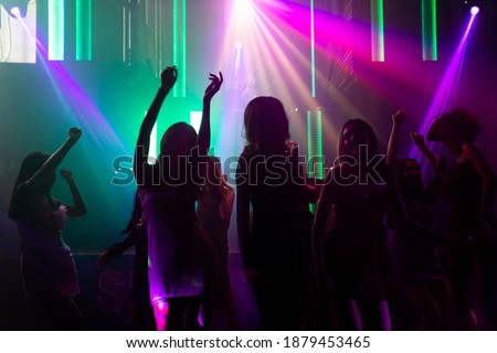 Silhouette image of people dance in disco night club to music from DJ on stage . New year night party and nightlife concept .