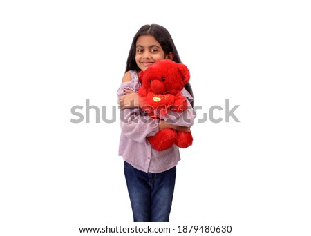 Cute little Indian girl hugging her favourite red teddy bear and smiling in white studio background. Royalty-Free Stock Photo #1879480630