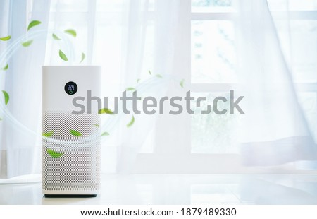 air purifier a living room,  air cleaner removing fine dust in house. protect PM 2.5 dust and air pollution concept Royalty-Free Stock Photo #1879489330