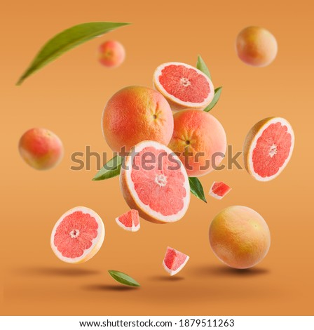 Flying in air fresh ripe whole and cut grapefruit with seeds and leaves isolated on red background. Royalty-Free Stock Photo #1879511263