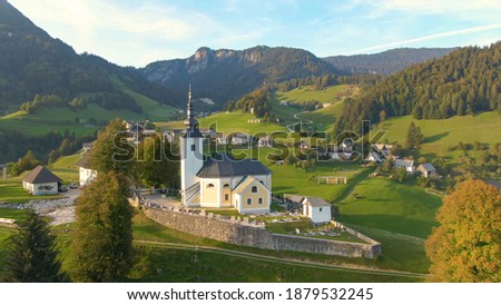 DRONE: Aerial view of the idyllic Slovenian countryside on a sunny autumn evening. Flying around a church and cemetery on top of a grassy hill overlooking the idyllic countryside in Soriska Planina. Royalty-Free Stock Photo #1879532245