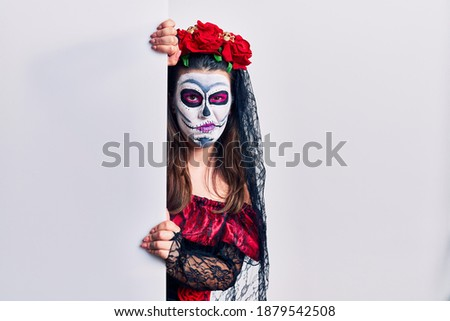 Young woman wearing day of the dead custome holding blank empty banner skeptic and nervous, frowning upset because of problem. negative person.