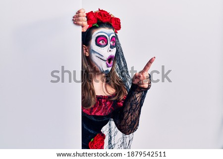 Young woman wearing day of the dead custome holding blank empty banner pointing with finger surprised ahead, open mouth amazed expression, something on the front
