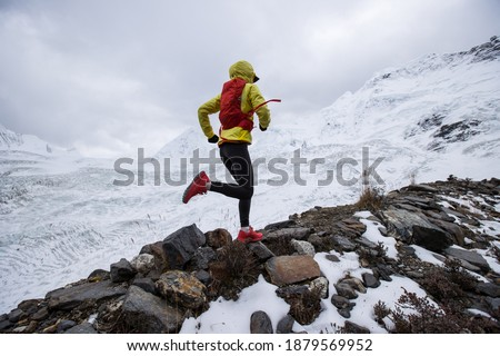 Woman trail runner cross country running up to winter snow mountain top Royalty-Free Stock Photo #1879569952
