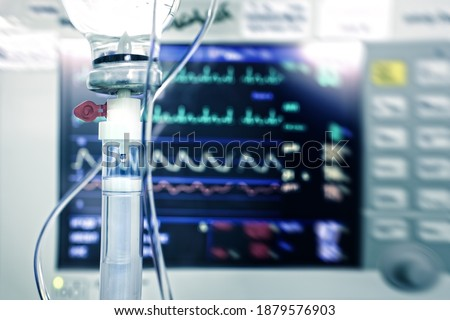 IV drip against the heart monitor as a concept of rescue emergency care in hospital. Royalty-Free Stock Photo #1879576903