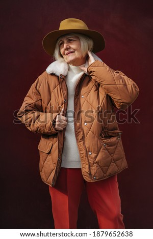 Senior woman in trendy outerwear and hat looking away while standing against vinous wall. Aged female in stylish outerwear Royalty-Free Stock Photo #1879652638