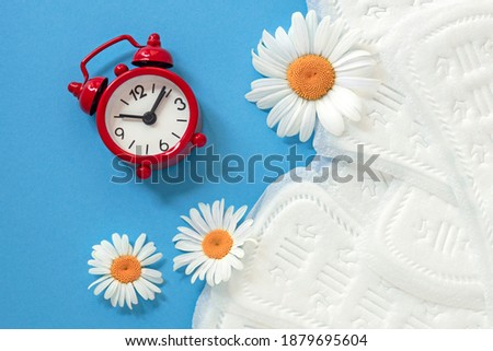 feminine sanitary pads, white chamomile flowers, alarm clock on blue background, concept of feminine health and hygiene, menopause, periodic menstruation Royalty-Free Stock Photo #1879695604