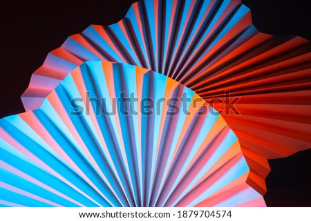 Background of paper fans of complex shape. Bright abstract background with dark base. Cardboard fans with a three-dimensional effect. Sometimes blurry image of three-dimensional geometric shapes. Royalty-Free Stock Photo #1879704574