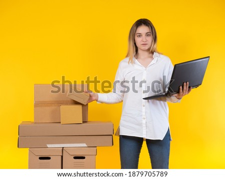 The girl works as a storekeeper. A woman with a laptop next to cardboard boxes. Warehouse storage of goods. Inventory in the warehouse. A woman checks the availability of goods.