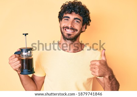 Handsome young man with curly hair and bear holding french coffee maker smiling happy and positive, thumb up doing excellent and approval sign