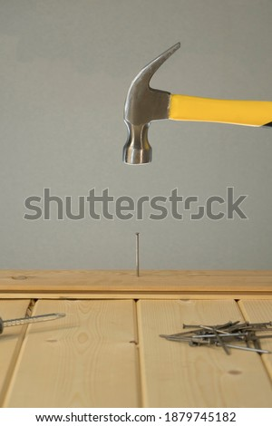 Hammer Hitting Nail On The Head. DIY. Carpenter hands with hammer wood and nail. Using hammer on wood backdrop. Tools for home repair. Fix the house. Close up of man hammering a nail into wooden board #1879745182