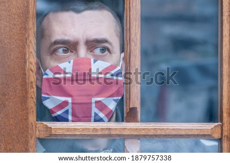 Young man in a protective mask with a British flag stays at home looking out the window. Lockdown in the UK. Corona virus mutated covid-19. Strengthening quarantine. Coronavirus is mutating. Health Royalty-Free Stock Photo #1879757338