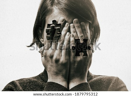 Self-destruction сoncept. Woman covers her face her hands on background with falling pieces of puzzle. Black and white image. Royalty-Free Stock Photo #1879795312