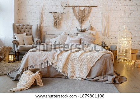 Front view of cozy bedroom with soft plaid and warmth blanket on comfortable bed, pillows, cushions, armchair, home decor and interior design in bohemian style Royalty-Free Stock Photo #1879801108