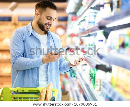 Smiling young man taking dairy products from shelf in the supermarket, holding bottle and smartphone, customer scanning bar code on product through mobile phone, walking with trolley cart