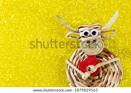 Ox with red heart on yellow background with sparkles. Christmas and New Year background. Symbol of year. Valentine's Day. Copy space