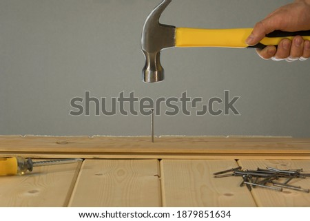 Hammer Hitting Nail On The Head. DIY. Carpenter hands with hammer wood and nail. Using hammer on wood backdrop. Tools for home repair. Fix the house. Close up of man hammering a nail into wooden board #1879851634