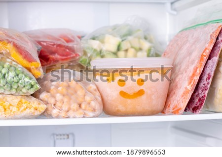 Frozen food in the freezer. Frozen vegetables, soup, ready meals in the freezer Royalty-Free Stock Photo #1879896553