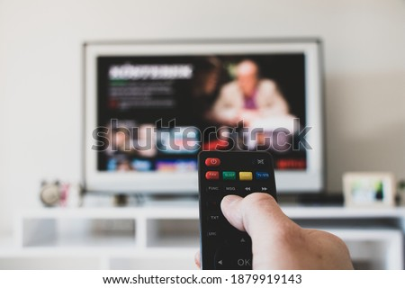 tv control room netflix etc. platform  and tv watching. smart watch tv controller changing channels. tv remote control changing channel netflix. remote control multimedia large resolution image.  #1879919143
