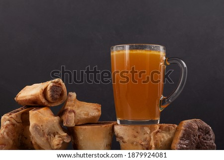 Homemade Beef Bone Broth in mug on dark background. Selective focus, copy space. Bones contain collagen, which provides the body with amino acids, which are building blocks of proteins. Royalty-Free Stock Photo #1879924081