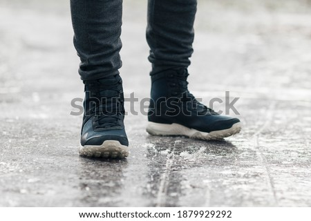 Dangerous icing on the sidewalk, slippery road. Royalty-Free Stock Photo #1879929292