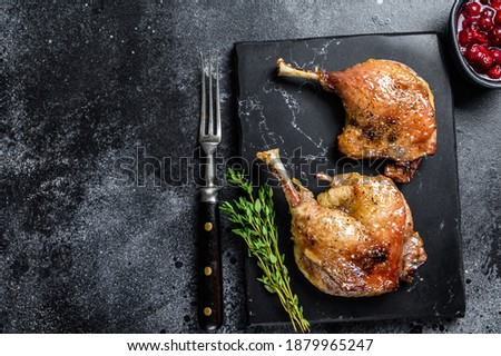 Roasted duck leg confit with cranberrie sauce. Black background. top view. Copy space