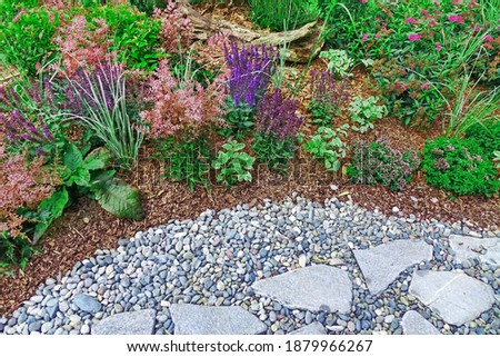 Backyard Garden Modern Designed Landscaping. Decorative Garden Design. Back Yard Lawn And Natural Mulched Border Between Grass, Plants And Pebble, Gravel Or Stone Walk Path. Royalty-Free Stock Photo #1879966267