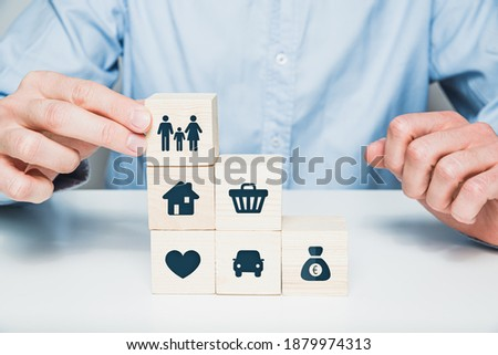 Man arranges wooden cubes with icons of money, car, health, family. Concept of prioritizing life, building a family.