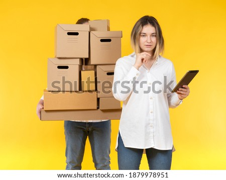 Inventory of  the warehouse. Woman with a tablet pc, man with a bunch of cardboard boxes. Accounting of goods in warehouse. Warehouse storage of goods. Storekeeper and loader on a yellow background.
