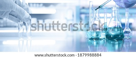 hand of scientist with test tube and flask in medical chemistry lab blue banner background Royalty-Free Stock Photo #1879988884