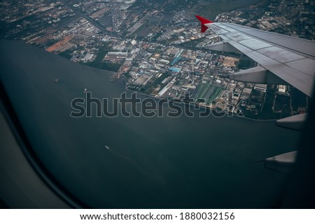 View from airplane window above the city and sea.flying and traveling #1880032156