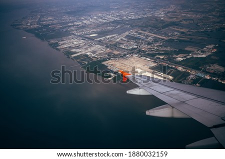 View from airplane window above the city and sea.flying and traveling #1880032159
