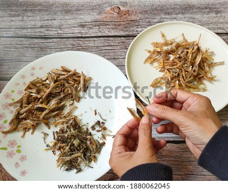 Dried anchovies.Popular ingredient in cooking in Southeast Asia countries.Picture showing removing bones before cooking.Selective focus.