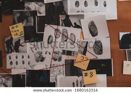 Detective board with crime scene photos, stickers, clues and red thread, closeup Royalty-Free Stock Photo #1880163316