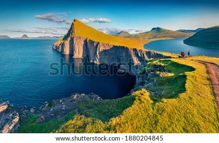 Trekking to Sorvagsvatn lake, Vagar, Faroe Islands, Denmark, Europe. Unbelievable summer seascape of Atlantic Ocean. Aerial landscape photography. Beauty of nature concept background. Royalty-Free Stock Photo #1880204845