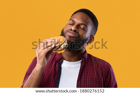 African Millennial Guy Smelling Tasty Burger Standing On Yellow Studio Background. Black Man Enjoying Eating Hamburger. Unhealthy Nutrition Habit, Overeating. Junk Food Lover Concept Royalty-Free Stock Photo #1880276152