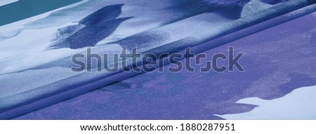 silk fabric, women's colored scarf with blue and white flowers. The gorgeous design is based on attractive background images. Texture background, pattern, postcard Royalty-Free Stock Photo #1880287951
